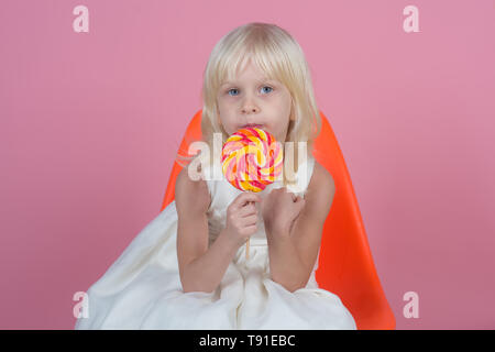 There is no resisting the sugary charms. Little child with sweet lollipop. Happy candy girl. Little girl hold lollipop on stick. Happy childhood food - Stock Photo