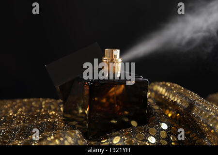 Bottle of perfume on sequin fabric against dark background - Stock Photo