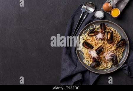 Mediterranean pasta with octopus, mussels and tomatoes souse in plate. Free space for text, background for banner - Stock Photo
