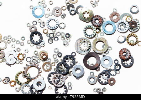 An assortment of metal washers scattered on a white background - Stock Photo