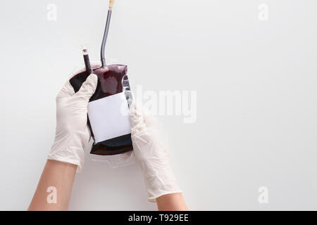 Hands in gloves holding blood pack for transfusion on white background - Stock Photo
