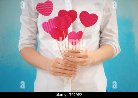 Woman holding sticks with paper hearts on color background - Stock Photo