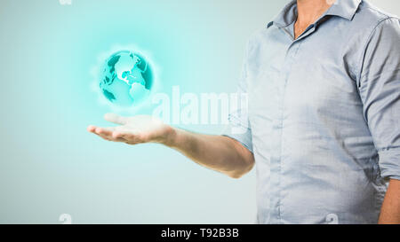 Casually dressed businessman holding virtual projection of the world in his hand  business/communications concept image. - Stock Photo