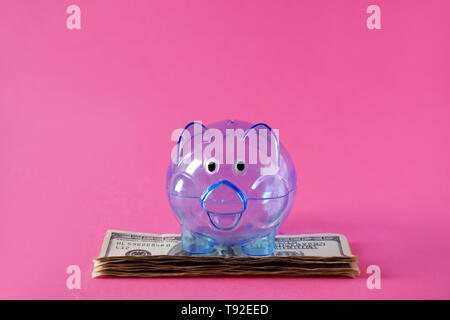 Piggy bank and dollars on color background - Stock Photo