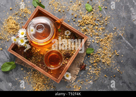 Hot tea with dried chamomile flowers in wooden box - Stock Photo
