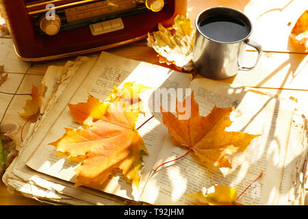 Old open book with retro radio and autumn leaves on wooden table - Stock Photo