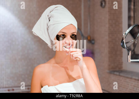 Portrait of a beautiful young woman after shower in patches. female brush teeth in front of her bathroom mirror. healty wellness morning concept.