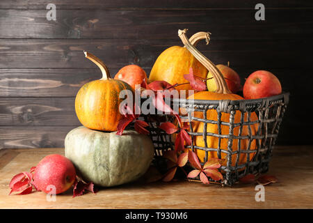 Basket with whole fresh pumpkins and apples on wooden table - Stock Photo
