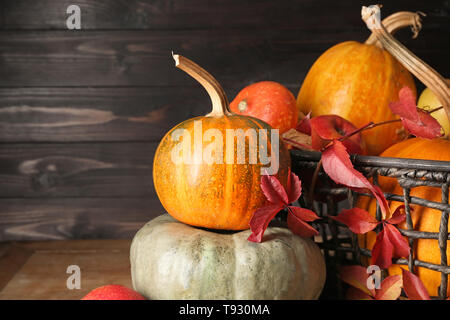 Whole fresh pumpkins with apples on wooden table - Stock Photo
