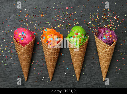 Waffle cones with delicious color ice cream and sprinkles on dark background - Stock Photo