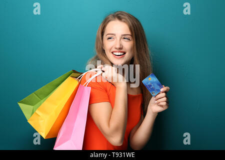 Happy beautiful woman with shopping bags and credit card on color background - Stock Photo