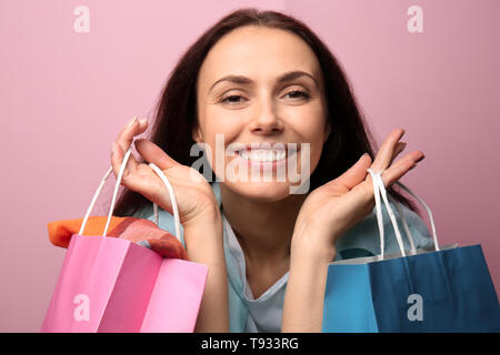 Happy girl with shopping bags on color background - Stock Photo