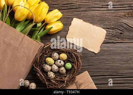Yellow tulips in a paper bag, a nest with Easter eggs on a wooden background. Top view with copy space. - Stock Photo