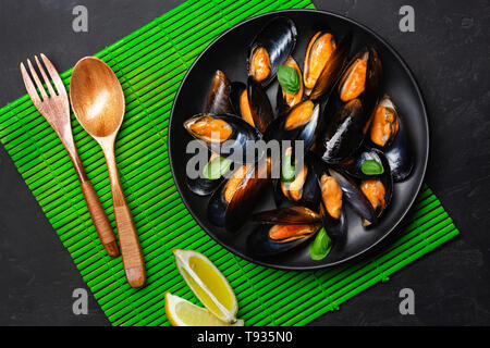 Seafood mussels and basil leaves in a black plate on bamboo mat and stone table. Top view. - Stock Photo