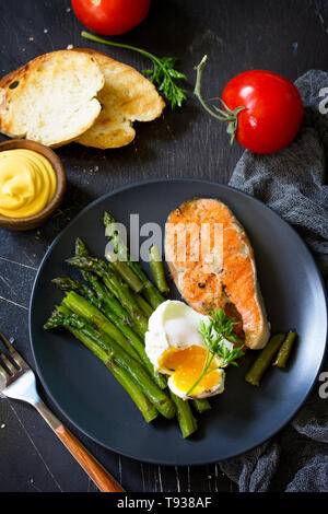 Salmon fish steak grilled with asparagus, poached egg on black background. Healthy food. - Stock Photo