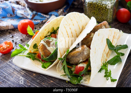 Delicious fresh homemade tortilla wrap with falafel and fresh salad on the table. Vegan tacos. Vegetarian healthy food. - Stock Photo