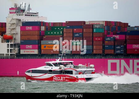 Red Funnel,Red Jet,passing,ONE,Hammersmith,container,ship,,out,of Cowes, Isle of Wight,The Solent, Southampton, England, UK, fast, passenger,ferry, - Stock Photo