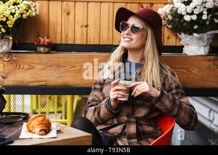 Beautiful young blonde stylish woman wearing a coat relaxing outdoors, holding takeaway cup - Stock Photo