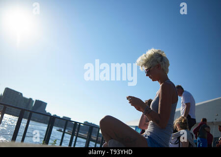 A young caucasian female sitting along the river shore in front of the Eye Filmmuseum in the city centre of Amsterdam in spring sunshine - Stock Photo