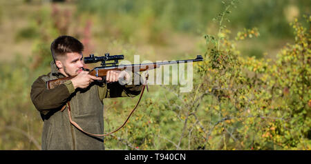 Bearded serious hunter spend leisure hunting. Hunter hold rifle. Hunting is brutal masculine hobby. Hunting and trapping seasons. Man brutal unshaved gamekeeper nature background. Hunting permit. - Stock Photo