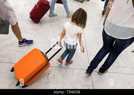 Little girl with head down pulling an orange trolley case in a hall of Orly Airport - Stock Photo