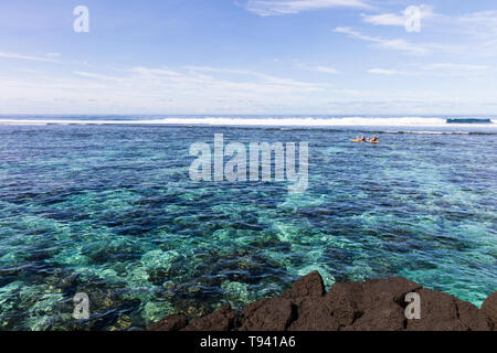 Family doing watersport kayak in clear pacific ocean water in the reef on a tropical island, Samoa, Polynesia.