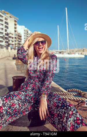 Happy fashionable mediterranean woman in hat laughing at harbour dock