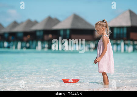 Cute child playing with paper boats in a sea - Stock Photo