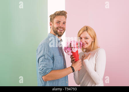 Man congratulates woman birthday anniversary holiday, pastel background. Couple in love celebrating holiday. Man gives bouquet flowers to girlfriend. Gift concept. Couple date bouquet flowers gift. - Stock Photo