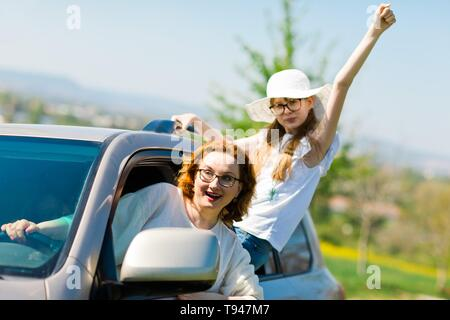 Rioters behind the wheel, female hooligans in the car showing gestures around - Stock Photo
