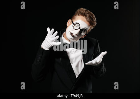 portrait of mime man in tuxedo and glasses on black background - Stock Photo