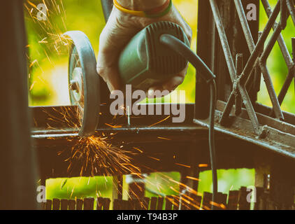 Man using angle grinder, cutting metal, a lot of flashing sparks are flying. - Stock Photo