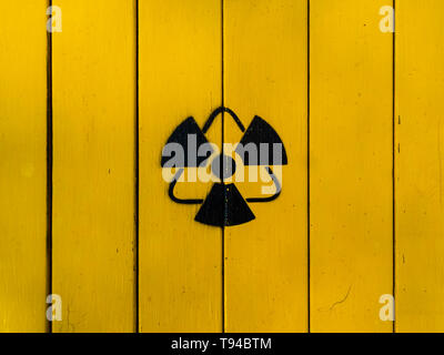 Sign of radiation on a yellow wooden board. Radioactive sign - symbol of radiation. Yellow and black radioactive hazard (ionizing radiation) nuclear d - Stock Photo