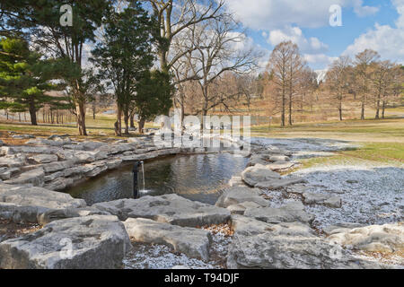 A little snow from the previous night lingers beside the Seven Pools Waterfall at Forest Park on a cold and blustery spring morning. - Stock Photo
