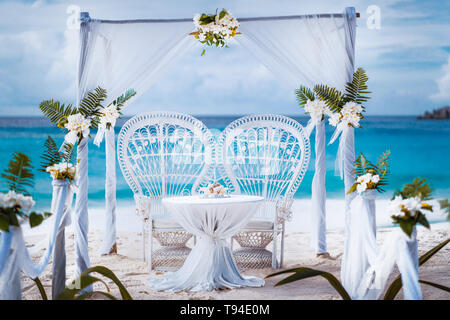 Beach wedding arch gazebo ceremonial decorated with white flowers on a tropical grand anse sand beach. Outdoor beach wedding setup. La Digue, Seychell - Stock Photo