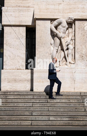 Milan, Italy, Europe: a businessman on the stairs of Palazzo Mezzanotte, or Palazzo della Borsa, the building housing the Milan Stock Exchange - Stock Photo