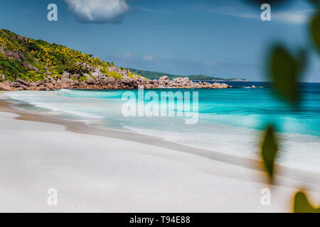 Petite Anse, La Digue in Seychelles. Tropcial, white sand paradise beach with turquise colored water on bright sanny day. - Stock Photo