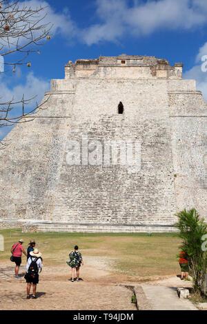 Uxmal Mexico, tourists at Uxmal maya ruins looking at the Pyramid of the Magician, Uxmal UNESCO World heritage site, Yucatan Mexico Latin America - Stock Photo