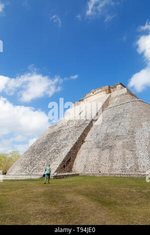 Mayan pyramid - a tourist looking up at the Pyramid of the Magician, travel and tourism; at mayan ruins at  UNESCO site of Uxmal, Mexico Latin America - Stock Photo