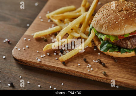 fresh golden french fries with tasty meat burger with scattered salt and black pepper on wooden chopping board - Stock Photo