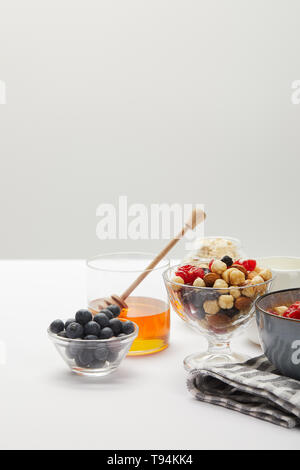 muesli with berries, nuts and honey in bowls served for breakfast on white table isolated on grey - Stock Photo