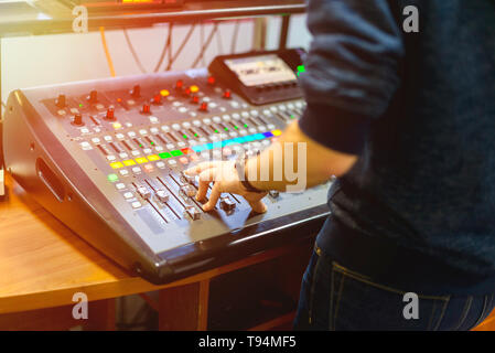 man using mixing console in sound recording studio - Stock Photo