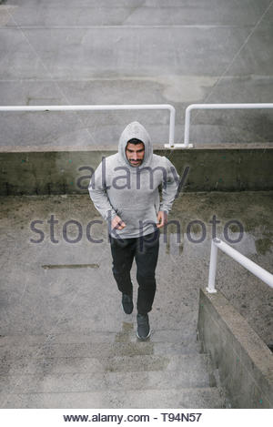 Urban athlete running upstairs under the rain. Banner of sporty man working out outside and climbing stairs in cold winter. - Stock Photo