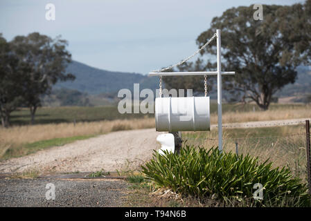 An old oil drum is converted into a large letterbox at the entrance to a rural property in north western New South Wales, Australia - Stock Photo