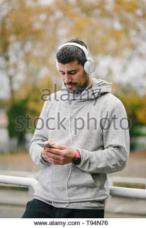 Fit man taking a running workout rest for texting on smartphone and listening music with headphones. Modern sport and running concept. - Stock Photo