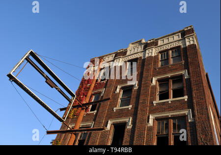 An abandoned, vacant apartment building, with many of its windows broken, is pictured in Detroit, Michigan. - Stock Photo