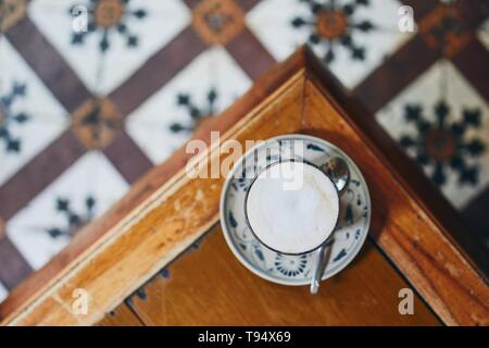 Cup of coffee on wooden table in cafe against retro style floor. Selective focus on foam. - Stock Photo