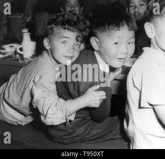 Entitled: 'A lunch hour scene at the Weill public school in the international section. Many children of Japanese ancestry like the boy shown here with his chum, were evacuated with their parents from this neighborhood.' The internment of Japanese-Americans during WWII was the forced relocation and incarceration in camps of 110,000-120,000 people of Japanese ancestry ordered by President Roosevelt shortly after Japan's attack on Pearl Harbor. - Stock Photo