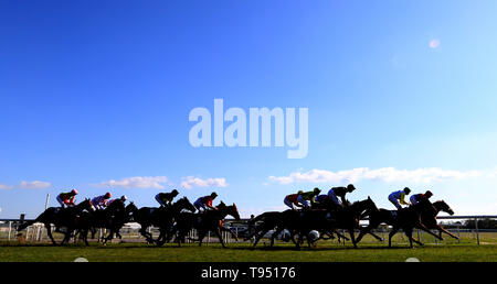 Runners and Riders round the first bend during The Investec Wealth Stakes during day two of the Dante Festival at York Racecourse. - Stock Photo