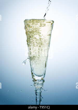 Pouring and overfill of Champagne on a fancy glass against a blue background - Stock Photo